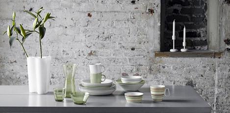 weiße Vase mit Pflanze auf Tisch mit arrangiertem Geschirr